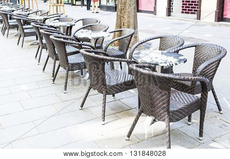 A row of small tables of a cafe on a pedestrian street