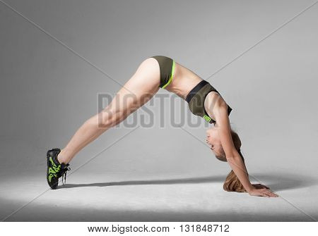 Caucasian Blond Woman In Dawn Dog Yoga Pose, Gray Background