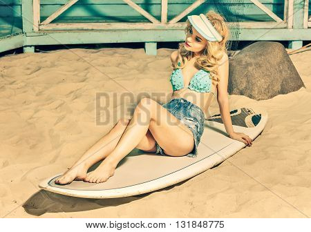 sexy blonde young woman in swimsuit and jeans shorts sitiing on serfboard on sand beach