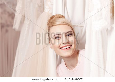 I want them all. Attractive young woman is looking though a variety of wedding dresses. She is smiling with happiness