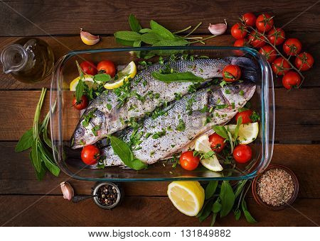 Two Raw Seabass In A Baking Dish With Spices On An Old Wooden Background. Top View
