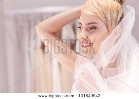 Happy future bride is wearing veil. She is looking forward and smiling