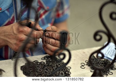 Master blacksmith engaged in assembling of metallic chainmail rings