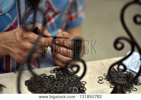 Master blacksmith engaged in assembling of metallic chainmail rings