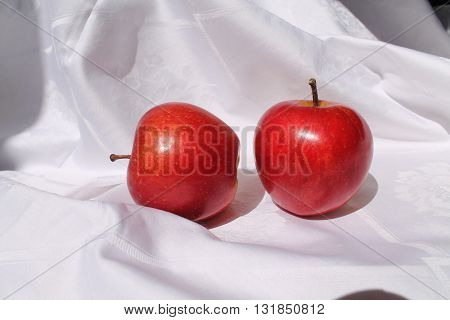 two red ripe sweet apples on the table