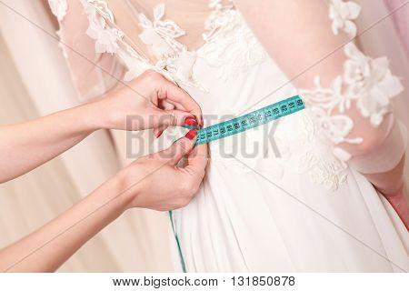 Close up of arms of tailor measuring female waist with tape-measure. Young bride is trying on a wedding dress