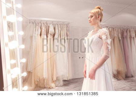 Attractive bride is wearing a white wedding dress. She is standing and dreaming. The lady is looking at mirror with joy