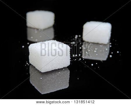 Sugar cubes on black background. Low key close-up.