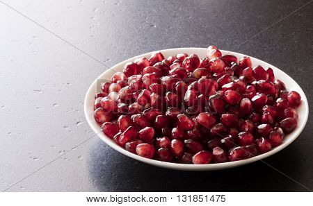 pomegranate seeds in a dish on a black stone table with free space at the left and top for text
