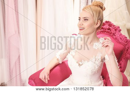 Beautiful young woman is sitting in chair in salon. She is wearing a wedding dress and smiling