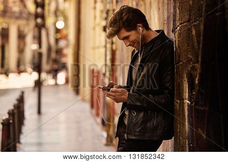 Young man listening music with smartphone earphones in the street