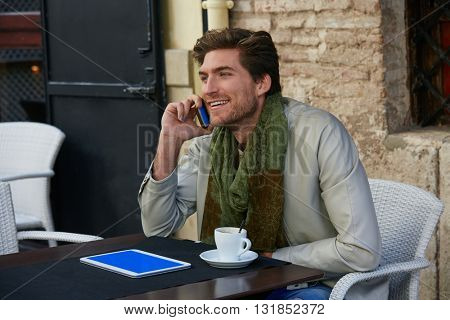 Young man talking smartphone phone in an cafe outdoor sitting having some coffe