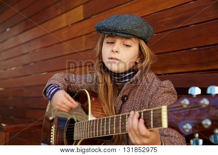 blond kid girl playing guitar with winter beret and coat on wooden background