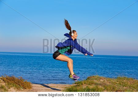 Runner girl jumping exercise in the beach dunes with headphones music