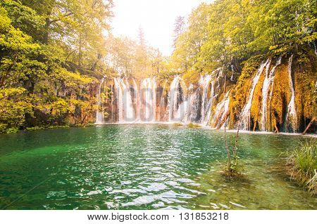 Beautiful landscape with waterfall in the Plitvice Lakes National Park in Croatia, warm sunlight filter applied, lens flare