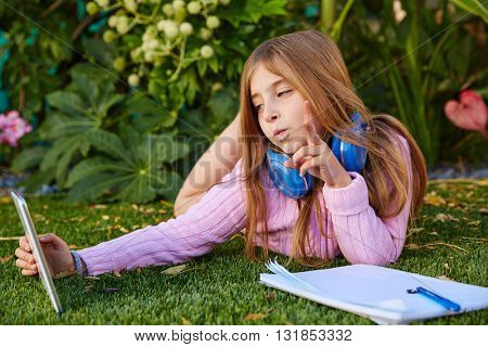 Blond kid girl selfie photo with tablet pc lying on grass turf with headphones