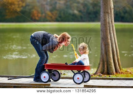 Kid girl and mother playing in the park lake with pull cart