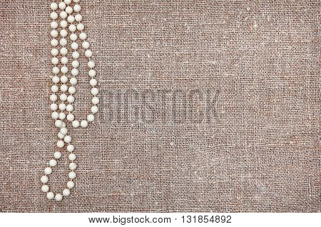 Vintage Background With Bead Necklace On The Old Burlap