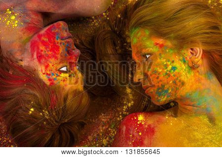 two beautiful women lying on the floor in the colors of Holi