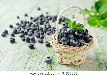 Freshly picked blueberries in a straw basket. Bilberry on wooden Background