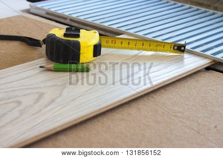 Measuring tape and a pencil on laminate floor plank