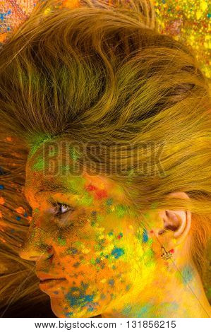 portrait of blond in colors of Holi, top view