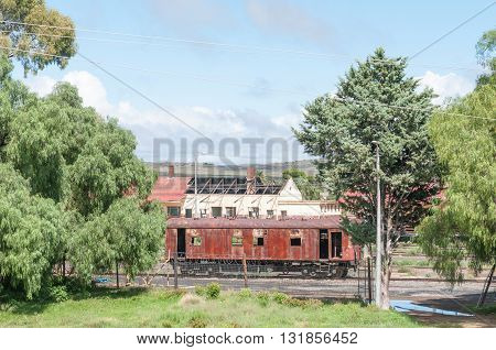 NOUPOORT SOUTH AFRICA - MARCH 8 2016: A rusted train coach and ruins of railroad infrastructure in Noupoort in the Northern Cape Karoo Region.