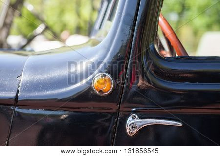 Color image of an old car door handle and a turn signal.