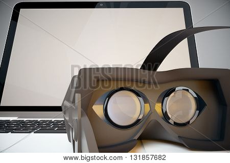 Closeup of virtual reality glasses next to laptop with blank screen. Mock up 3D Rendering