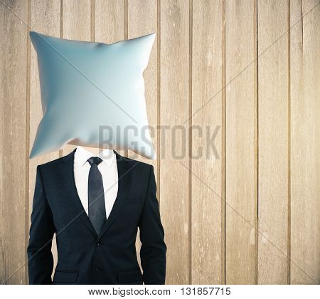 Pillow headed businessman on wooden plank background. Mock up