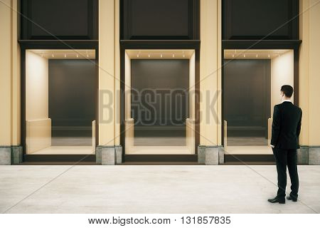 Front view of shop exterior design with glass showcase and looking businessman. Mock up 3D Rendering