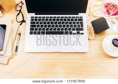 Top view of girly designer desktop with flower laptop coffee cup glasses and office tools