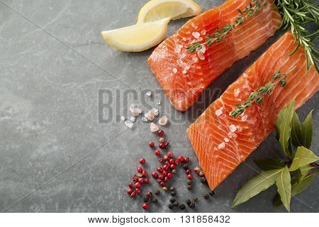 Selection of Herbs and Spices with fresh fillets of raw pink trout on a grey slate background. Ingredients includes pink salt black peppercorns fresh thyme fresh rosemary lemon wedges pink peppercorns bay leaves. With Copy Space shot overhead