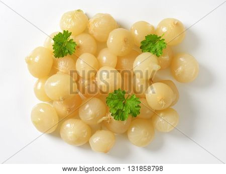 heap of small pickled onions with parsley on white background