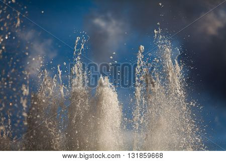 Splashing streams of fountains on background of a sky