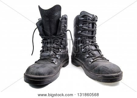 Old dirty army boots made of black leather on white background