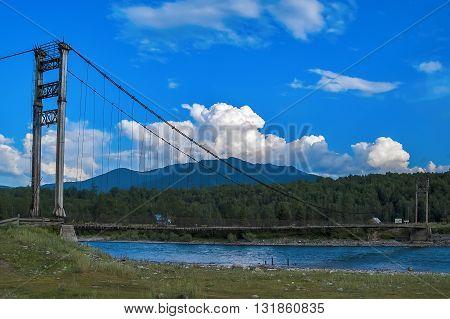 Tyungur, Russia - July 23, 2005: Suspension road bridge on the river Katun. Altai Mountains