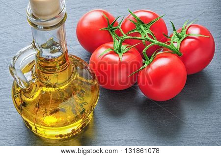 Bottle of olive oil with herbs and red tomatoes on black slate stone
