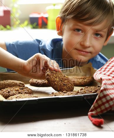 blond boy eating oatmeal cookies on kitchen