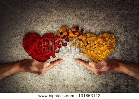 Two human hands holding rose petal hearts on concrete background. Romantic relationship concept. Attachment and love symbol giving and exchange of feelings and emotions of love.