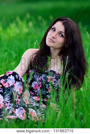 Very beautiful, attractive, lovely, cute, awesome, gorgeous, pretty, excellent, perfect girl sitting in the green grass. Beautiful girl has picnic in park. Attractive girl in green forest, garden, greenery summer