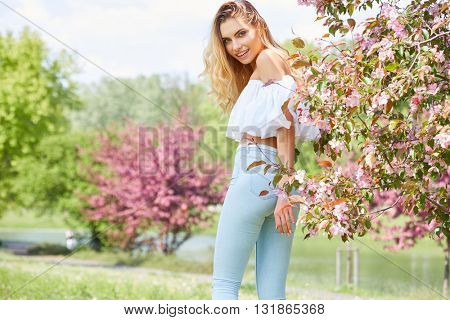Beautiful happy young woman enjoying smell in a flowering spring garden