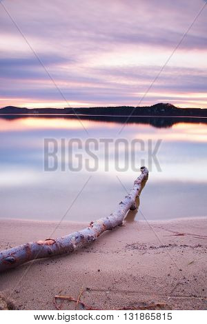 Long Exposure Of Lake Shore With Dead Tree Trunk Fallen Into Water Autumn Evening After Sunset.