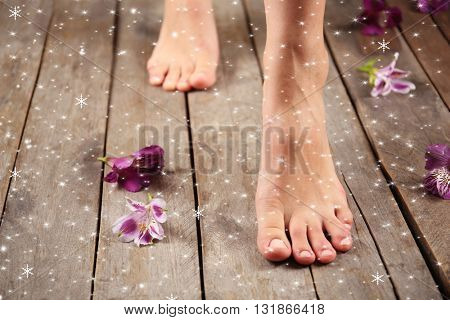 Female feet and flowers on wooden background with snow effect