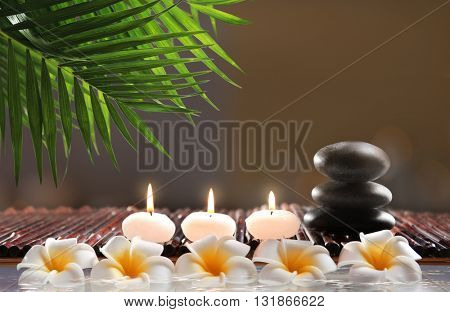 Composition with spa stones, flowers and candles in water on blurred background