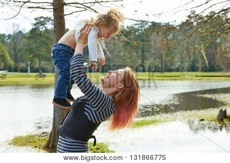 Mother playing throwing up baby girl daughter in the park lake