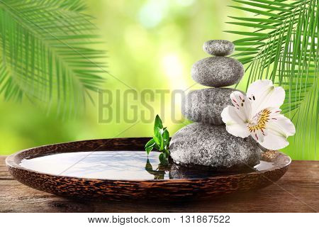 Composition with spa stones and flower on natural blurred background