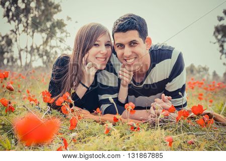 Young Couple Lying On The Grass In A Field Of Red Poppies And Smiling At The Camera