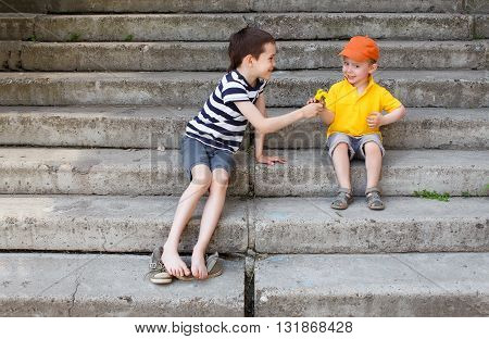 friendship. cute boy gives a bouquet of dandelions little child. copy space for your text