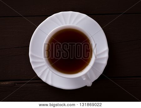 Cup of tea on brown wooden background view from above.
